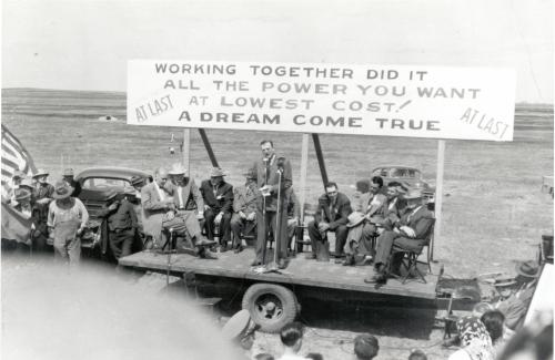 Photo from NRECA, image shows sign that reads working together did it all the power you want at lowest cost! A dream come true, at a celebration ceremony